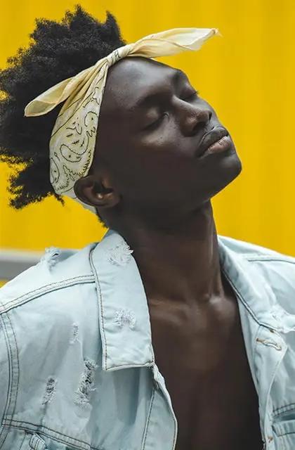 Homem negro, de camisa jeans aberta e lenço na testa, cabelos crespos e médios, olhos fechados, fundo amarelo, ilustra tipo de pele oleosa.