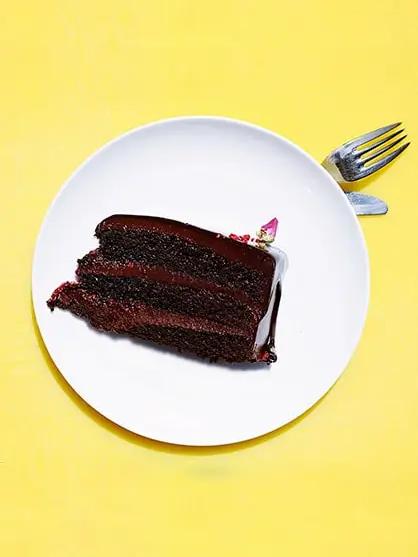 Foto de bolo de chocolate em camadas, em prato branco, fundo amarelo e garfo, para ilustrar as camadas da pele: epiderme, derme e hipoderme.