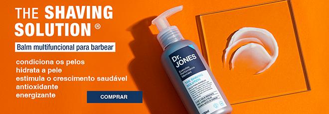 """Na imagem em fundo laranja, vê-se embalagem do produto The Shaving Solution - Balm multifuncional para barbear, da Dr. JONES. Esta frase e a frase: """"condiciona os pelos, hidrata a pele, estimula o crescimento saudável, antioxidante e energizante' com o botão """"Comprar"""" em fundo azul complementam a foto."""