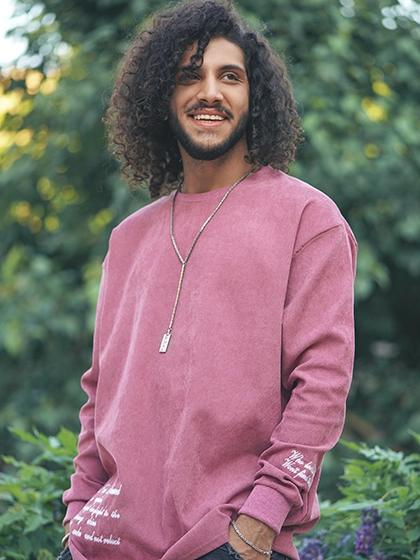 Foto de homem pardo de cabelos médios encaracolados e barba aparada. Ele sorri e usa calça jeans e blusa rosada, para aludir ao tratamento bem-sucedido com o climbazol em shampoos anticaspa.
