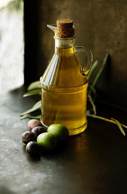 Em artigo sobre pele oleosa, que fala sobre hábitos que pioram a oleosidade da pele, imagem mostra uma jarra de azeite de oliva em cima de uma mesa de madeira, cercado de azeitonas.