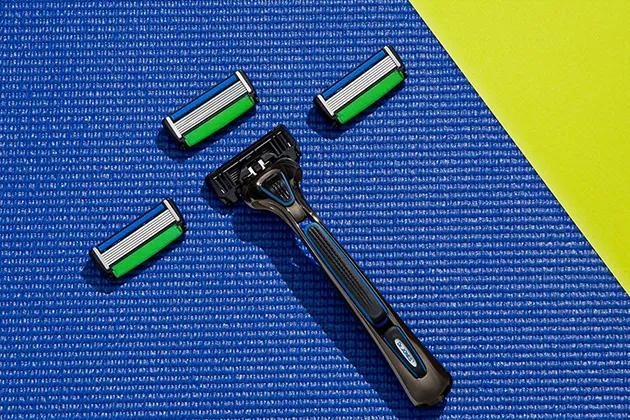 Em artigo sobre funcionalidades secretas do THE RAZOR, da Dr. JONES, imagem traz o aparelho de barbear com três lâminas em fundo texturizado azul e verde limão.