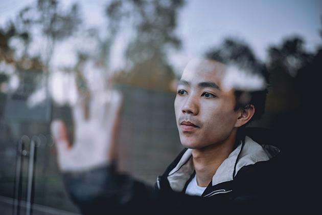 Homem oriental com agasalho azul e camiseta branca atrás de janela fechada, mão esquerda no vidro, olhando para fora.