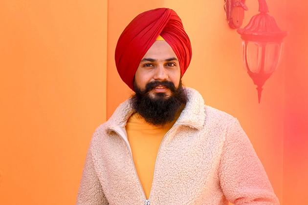 Em artigo sobre falhas na barba, imagem mostra um indiano sikh, com barba escura bastante longa, casaco branco, camisa amarela e turbante vermelho, em frente a parede laranja.