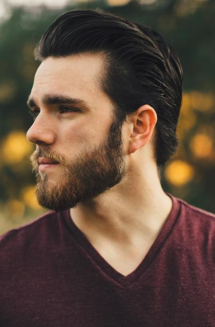 Homem de pele clara, com barba, cabelo escuro para trás estruturado com pomada de cabelo, camisa vinho, em frente a uma árvore com sol ao fundo. Foto idêntica à da abertura do artigo.