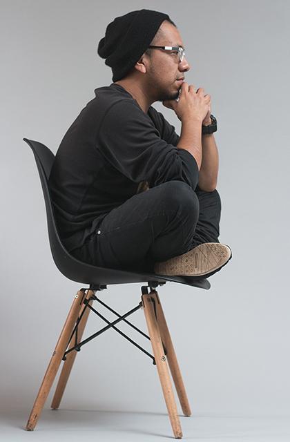 Homem negro usando óculos, de touca preta, agasalho preto e jeans escuro, sentado em cadeira com as mãos no queixo, barba a fazer, ilustra artigo sobre coceira na barba.