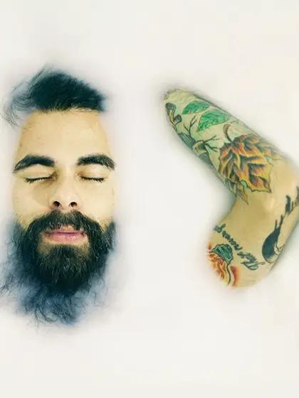 Em artigo sobre autocuidado para portadores de HIV e aids, foto mostra homem branco com barba mergulhado em líquido branco espesso. Vê-se seu rosto e o braço esquerdo, que tem tatuagens.