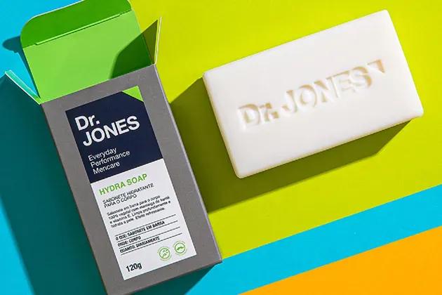 Foto de embalagem e barra do sabonete natural Hydra Soap, da Dr. JONES, em fundo verde, azul-turquesa e laranja. O sabonete masculino traz, entre os ingredientes, a manteiga de karité.
