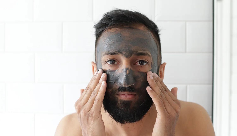 Homem de pele clara e de cabelos, olhos e barba escuros, sem camisa, passa no rosto pasta de carvão vegetal.