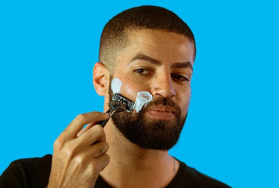 Em fundo azul, foto de homem de pele clara, camiseta preta, sardas e cabelo raspado fazendo a barba com a espuma de barbear PRECISION FOAM e com o aparelho THE RAZOR, da Dr. JONES.