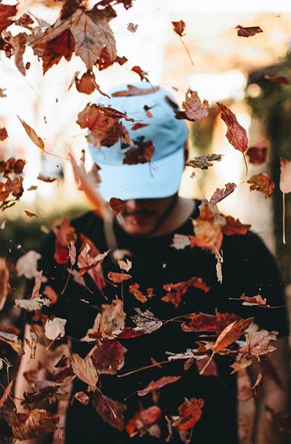 Em artigo sobre queda de cabelo e calvície, homem de camiseta preta e boné azul claro, de barba e cabeça baixa, caminha em meio a folhas de outono que caem.