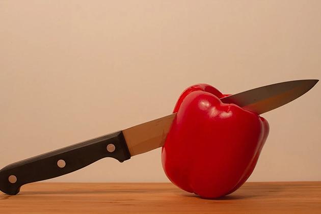 Em artigo sobre irritação na pele após fazer a barba, imagem mostra uma faca com cabo de madeira cortando ao meio um pimentão vermelho, em uma mesa de madeira e com fundo bege.