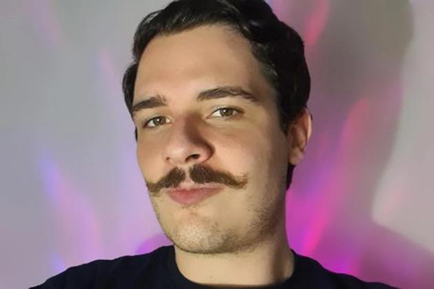 Gustavo Aguera, cientista de dados da Dr. JONES, tem pele clara, bigode curvo, olhos verdes e cabelos ondulados castanhos. Veste camiseta azul em fundo neutro cinza com luzes.