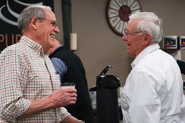 Dois homens idosos conversando.Um deles, de camisa quadriculada e segurando um copo com café, sorri ao outro, de camisa branca. Ambos caucasianos, usam óculos e têm cabelos grisalhos.