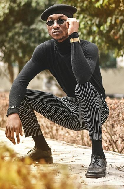 Foto de homem negro usando blusa preta, calça listrada preta e branca, sapatos pretos e óculos escuros e boina preta.