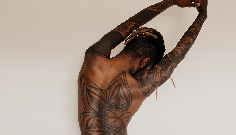 Homem negro, cabelo raspado na lateral, com tranças descoloridas. Ele está de costas, que são tatuadas, alongando-as, em frente a um fundo de cor clara.
