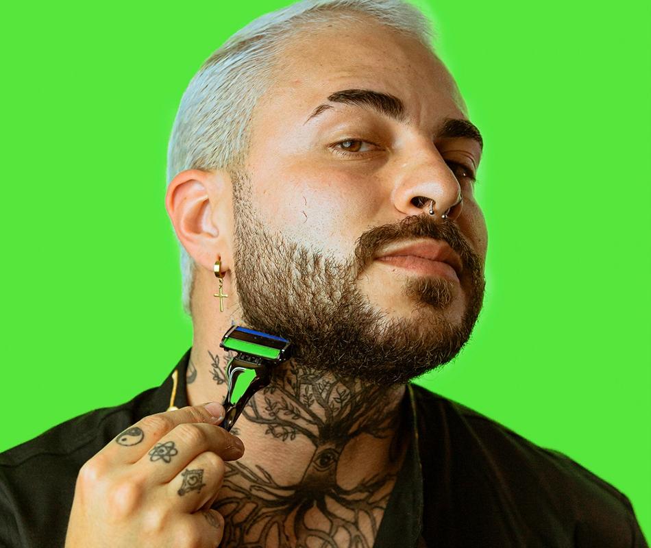 Em artigo sobre funcionalidades secretas do THE RAZOR, da Dr. JONES, foto de homem de pele clara, tatuagem em formato de árvore no pescoço, barba desenhada escura e cabelos platinados usando o aparelho de barbear. O fundo é verde-claro.