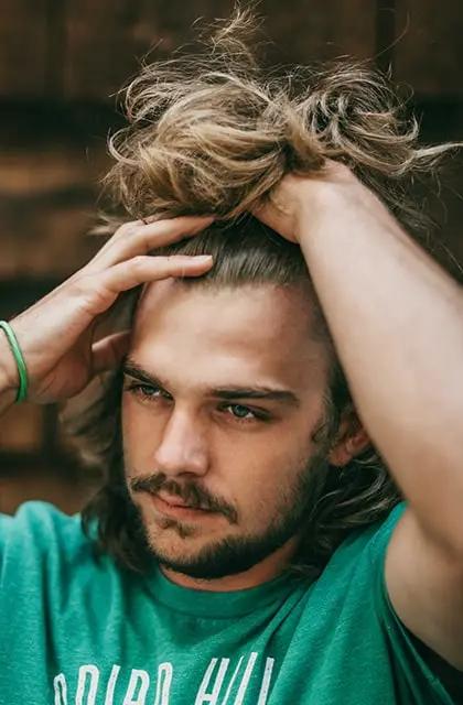 Foto de homem loiro e olhos claros usando camisa verde e barba. Ele pega os cabelos, compridos, e, usando as mãos, os puxas para cima, exibindo a força dos cabelos e a grande quantidade de fios.