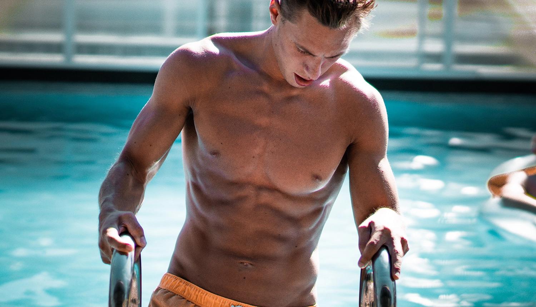 Rapaz com bermuda laranja, sem camisa e peito sem pelos, pele clara e cabelos castanhos claros, sai de uma piscina, ilustrando texto sobre dicas para depilar o peitoral.