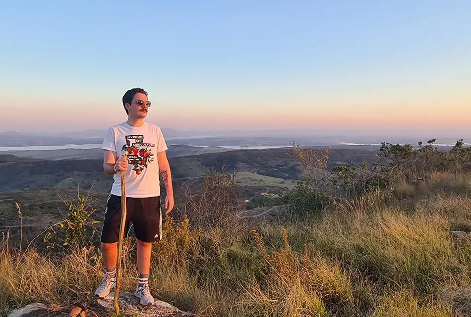 Em paisagem sobre colina, Gustavo Aguera veste camiseta branca, bermuda preta com listras brancas, tênis branco e óculos escuros e segura um pedaço de madeira. Ao fundo, a paisagem mostra cursos d'água e a planície.