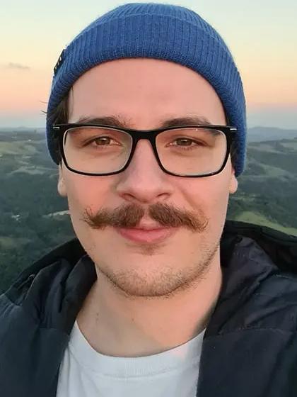 Gustavo Aguera em frente a paisagem em colina, usando camiseta branca, gorro azul, jaqueta cinza e óculos de armação preta.