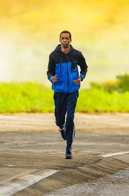 Em artigo sobre autocuidado para portadores de HIV e aids, foto mostra homem negro correndo sobre uma pista e vestindo agasalho azul e calça azul. Ao fundo, há paisagem com mata.