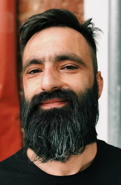 Em artigo sobre falhas na barba, imagem mostra um homem de camiseta preta, pele clara, barba escura, longa e densa, semigrisalha, com leve sorriso.