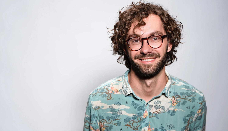 Homem de óculos redondos marrons sorrindo, pele clara, camisa estampada azul-clara, fundo branco, barba aparada e cabelos castanhos claros de tamanho médio e com 'entradas' em artigo sobre queda de cabelo e calvície.