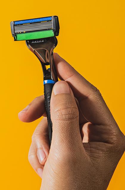 Mão segura o THE RAZOR, aparelho de barbear da Dr. JONES, em frente a fundo amarelo.