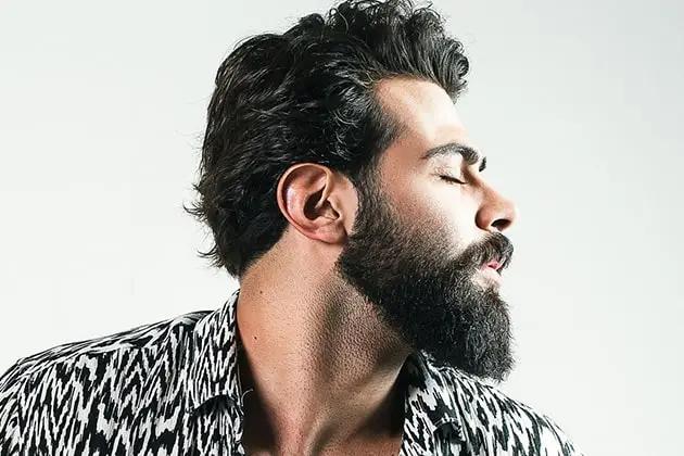 Em artigo sobre como tirar frizz da barba, imagem mostra homem de ascendência árabe e pele clara, barba quadrada e bem alinhada, de olhos fechados e cabelos escuros, virado para o lado direito. Ele usa camisa estampada preta e branca.