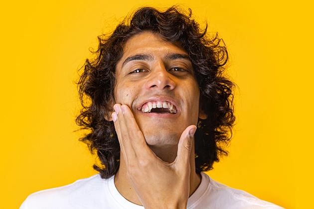 Em artigo sobre skincare (cuidados com a pele masculina), imagem em fundo amarelo traz homem de pele parda, olhos castanhos e cabelo cacheado médio e castanho sorrindo, com as mãos no queixo, na região da barba.