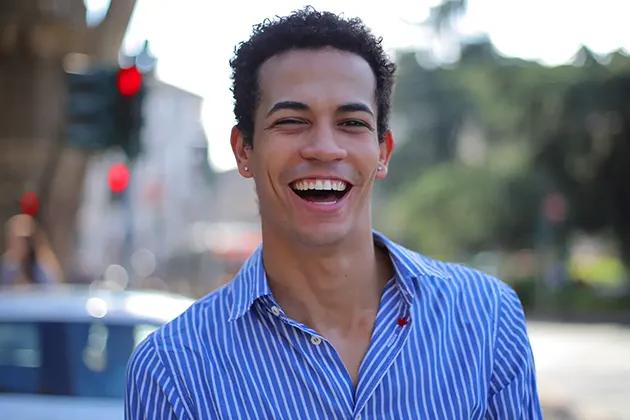 Foto de homem sem barba na rua, cabelos escuros, cacheados e bem curtos, camisa listrada de fundo azul e listras brancas, pardo, sorrindo. A imagem faz alusão ao melhor barbear, sem irritação na pele.