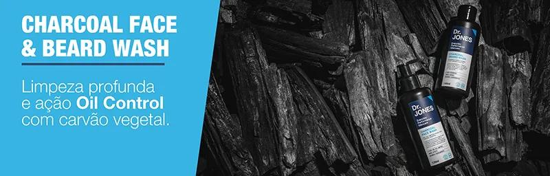 Foto de produtos da Linha Charcoal, da Dr. JONES, feitos com carvão vegetal. As embalagens (duas), pretas, encontram-se em cima de carvões. Do lado esquerdo, em fundo azul e letras brancas, lê-se Charcoal Face & Beard Wash: limpeza profunda e ação Oil Control com carvão vegetal.