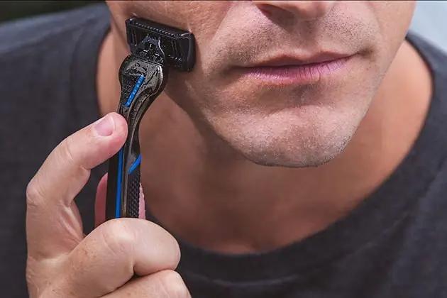 Foto de detalhe de rosto de homem branco passando o barbeador THE RAZOR, da Dr. JONES, com balm para barba THE SHAVING SOLUTION.