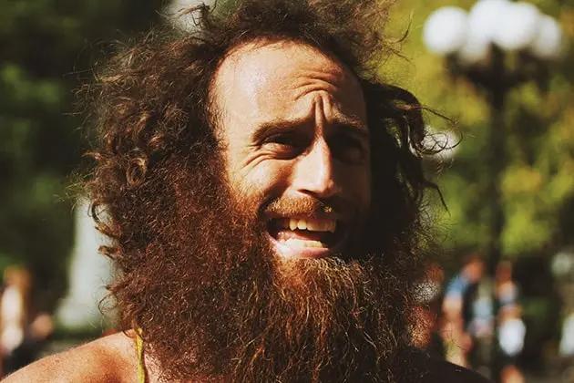 Em artigo sobre frizz na barba ('barba crespa'), imagem mostra homem fazendo careta, pele clara, barba e cabelos bem desgrenhados e grandes, com bastante frizz, em meio a uma praça.
