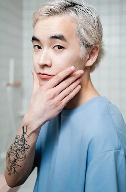 Homem jovem oriental de camiseta azul-clara, braço tatuado e cabelos descoloridos, passa a mão no queixo para ilustrar o tipo de pele normal.