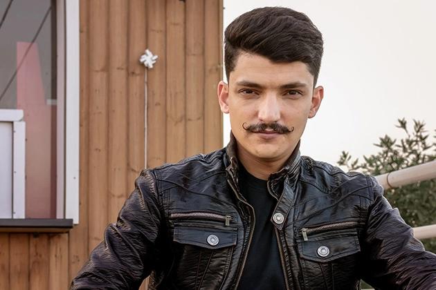 Em artigo sobre sete estilos de bigode para inovar no visual, imagem traz homem jovem em frente a casa de madeira, pele parda, de bigode encurvado para cima, jaqueta de couro e cabelos curtos e escuros.