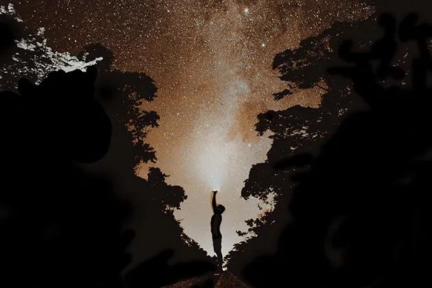 Foto de sombra de homem ladeado por mata, à noite, acima do qual se vê o céu estrelado.