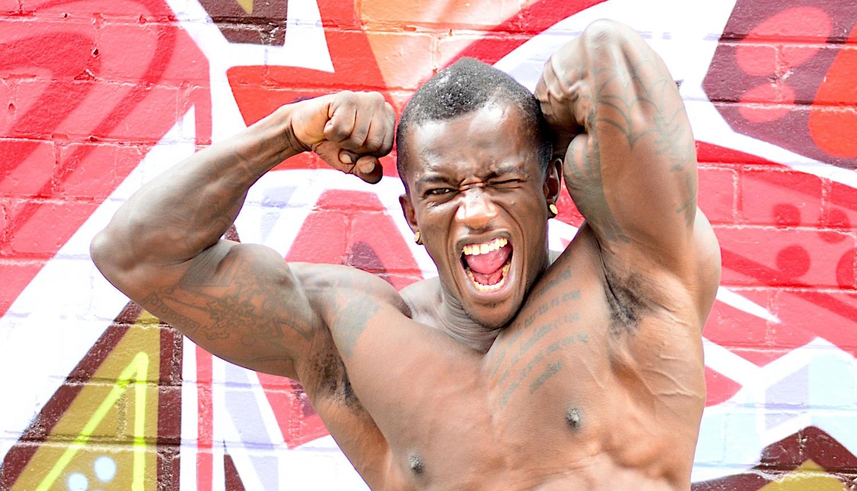 Em artigo sobre como calcular proteínas para ter massa muscular, homem negro de torso nu põe braços às costas, músculos evidentes, em frente a parede com graffiti.