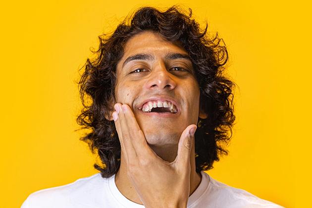 Em artigo sobre skincare (cuidados com a pele masculina), imagem em fundo amarelo traz homem de pele parda, olhos castanhos e cabelo cacheado médio e castanho sorrindo, com as mãos no queixo.