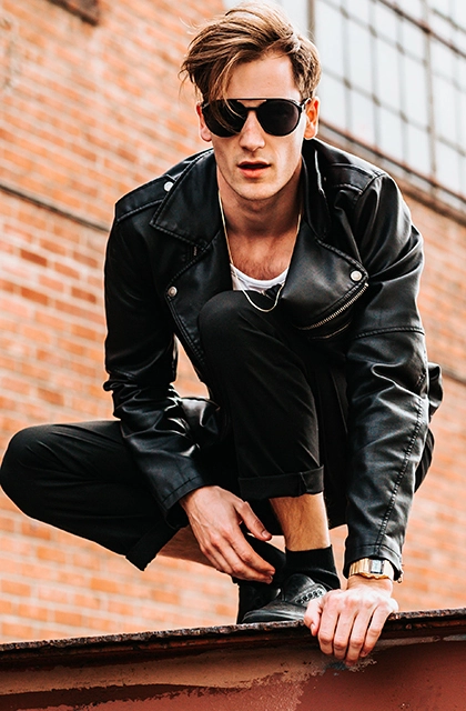 Foto de homem loiro, pele clara, cabelo liso, usando calça preta, botina preta e jaqueta de couro preta, com camiseta branca por baixo. No rosto, ele usa também óculos escuros.