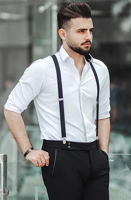 Foto de homem árabe, pele clara, cabelos lisos e curtos, usando camisa branca, calça de alfaiataria preta e suspensório preto.