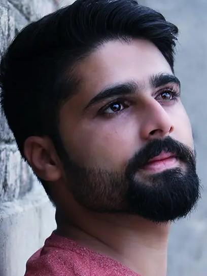 Foto de homem árabe, pele clara, cabelos escuros e barba cheia escura, encostado em parede e olhando para a esquerda, usando camisa salmão.