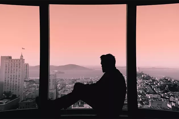 Sombra de homem sentado, corpo inteiro, pernas dobradas, no parapeito de ampla janela fechada dividida em três partes, olhando para fora. Ao fundo, grande cidade costeira, com prédio alto em destaque. Foto em degradê de vermelho e preto e branco.