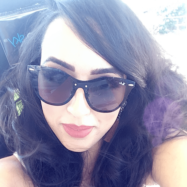Natália de Lucca, analista de produtos da Dr. JONES, tem pele clara e usa batom vermelho, cabelos longos escuros e óculos escuros. A foto destaca o rosto, dentro de um carro com paisagem ao fundo.