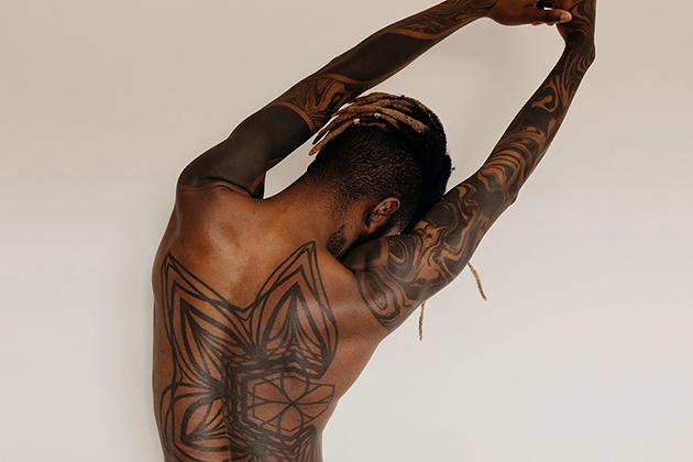 Homem negro, cabelo raspado na lateral, com tranças descoloridas. Ele está de costas, que são tatuadas, alongando-as, em frente a um fundo de cor clara, em artigo sobre série de exercícios para dor nas costas.