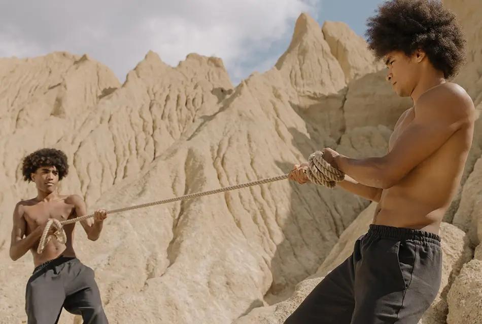 Em deserto, imagem de dois rapazes negros, sem camisa e de bermuda, puxando cada um a extremidade de uma corda, representando a força do cabelo.
