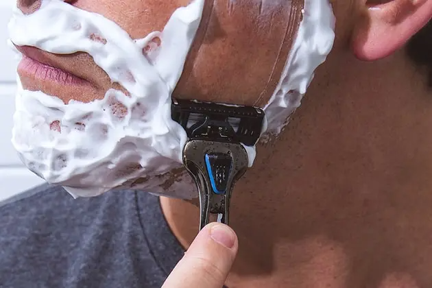 Foto de detalhe de rosto de homem branco passando o barbeador THE RAZOR, da Dr. JONES, com espuma de barbear PRECISION FOAM.