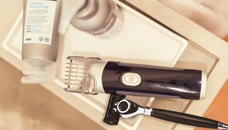 ISOTONIC FACE SCRUB, THE SHAVING SOLUTION e THE RAZOR, produtos da Dr. JONES, ao lado de barbeador elétrico, em pia de banheiro. A foto tem tons pastéis, tendendo para bege e rosa.