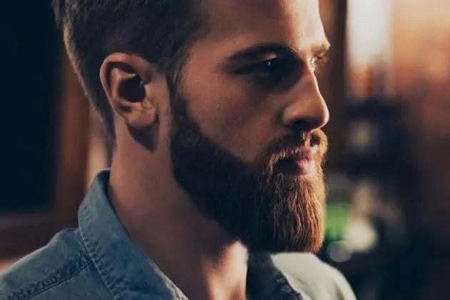 Em artigo sobre quatro estilos de barba para se inspirar, imagem traz homem vestido camisa jeans, com barba desenhada, longa e quadrada, de pele clara e cabelos castanho-claros, de perfil.
